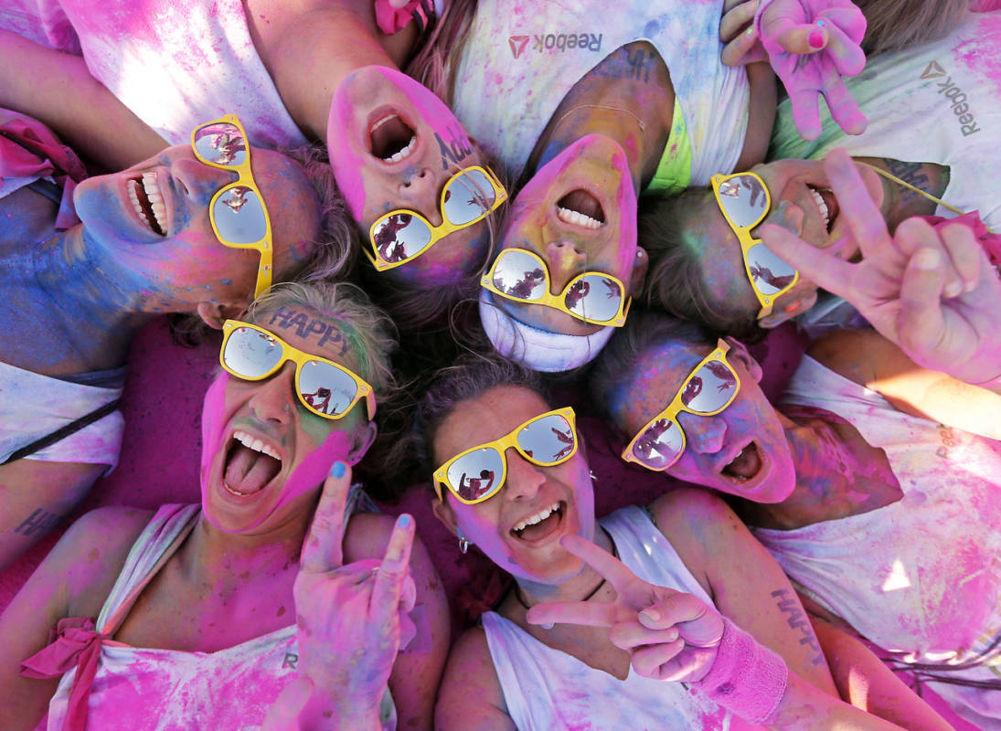 Competitors covered in coloured powder react after crossing the finish line during the Color Run in Marseille